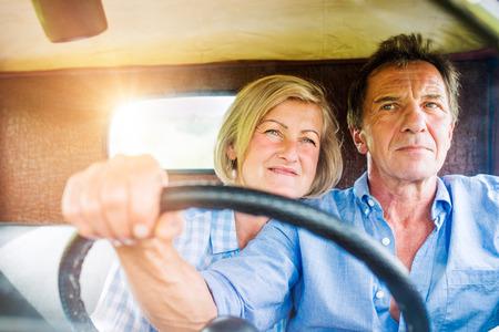 Schließen Sie oben von den älteren Paaren innerhalb eines Kleintransporters, der Mann, der ein Lenkrad hält