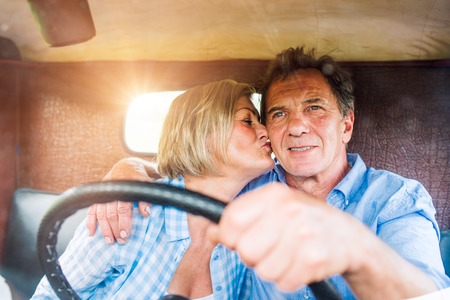 holding close: Close up of senior couple inside a pickup truck, man holding a steering wheel, woman kissing him