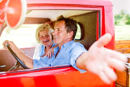reach truck: Close up of senior couple inside a red pickup truck, man holding a steering wheel, stretching out his arm Stock Photo