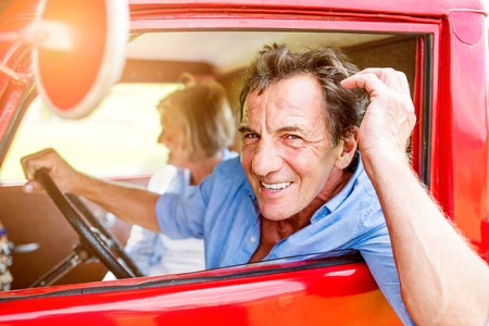 leaning on the truck: Close up of senior couple inside a red pickup truck, man holding a steering wheel, doing his hair