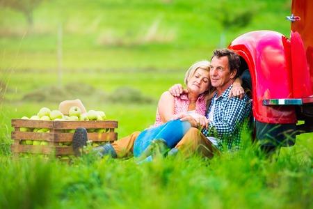 transport truck: Senior couple harvesting fruit, sitting on grass at red vintage pickup truck, hugging Stock Photo