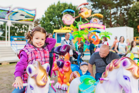fun fair: Little girl enjoying  a pony ride at fun fair, amusement park