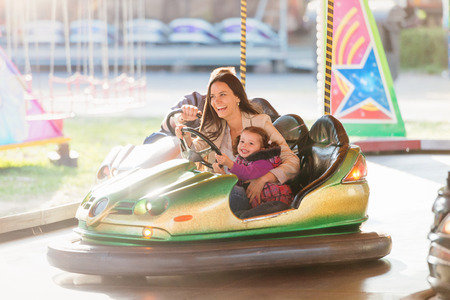 Cute little girl with her mother having fun at fun fair, driving a bumper car, amusement park Imagens