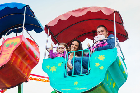 family in park: Cute little girls with their mother and father enjoying ride at fun fair, young family, amusement park Stock Photo