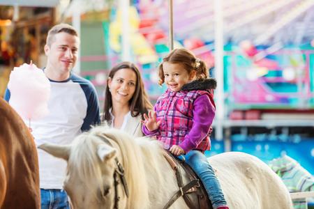 Dziewczynka cieszy się na przejażdżkę kucykiem na targach zabawy, rodzice patrząc na nią, park rozrywki