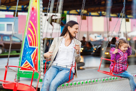 chain swing ride: Cute little girl with her mother having fun at fun fair, chain swing ride, amusement park Stock Photo