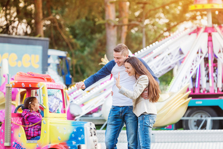 family in park: Parents at fun fair, waving their child taking ride, amusement park Stock Photo