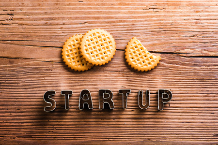 galletas: Office desk with start up sign made of cookie cutters and biscuits. Flat lay. Workplace