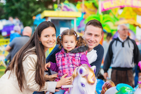 family in park: Cute little girl with her mother and father enjoying ride at fun fair, amusement park