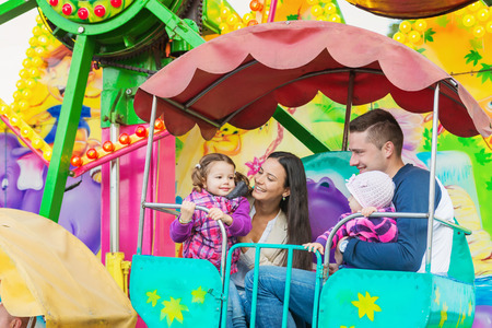 Cute little girls with their mother and father enjoying ride at fun fair, young family, amusement park Stock Photo