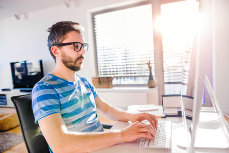 Man sitting at the desk working from home on computer, writing on keyboard Stock Photo