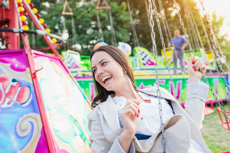 chain swing ride: Young woman having fun at fun fair, chain swing ride, amusement park Stock Photo