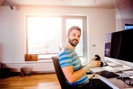 trabajando en casa: El hombre sentado en el escritorio con el ordenador y la tableta gráfica, trabajando desde su casa, sosteniendo la cámara