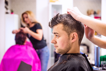 man haircut: Unrecognizable professional hairdresser making new haircut to her handsome client. Barber at work. Man at barbershop.