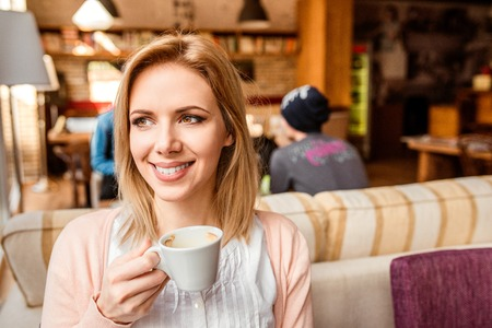 enjoing: Young beautiful woman in cafe drinking coffee, enjoing her espresso and relaxing Stock Photo