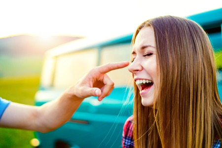 campervan: Young teenage couple in love, boy and girl, boyfriend and girlfriend, man touching womans nose, laughing, old green campervan Stock Photo