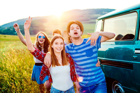grass and sky: Young teenage hipster frieds with campervan having fun, against green nature and blue sky, hands up, arms raised Stock Photo