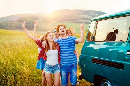 manos levantadas al cielo: inconformista adolescente frieds con caravana que se divierten, contra la naturaleza verde y el azul cielo, las manos, los brazos levantados Foto de archivo