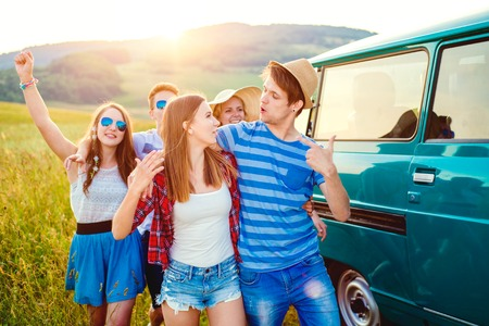 campervan: Young teenage hipster frieds with campervan having fun, against green nature and blue sky, hands up, arms raised Stock Photo