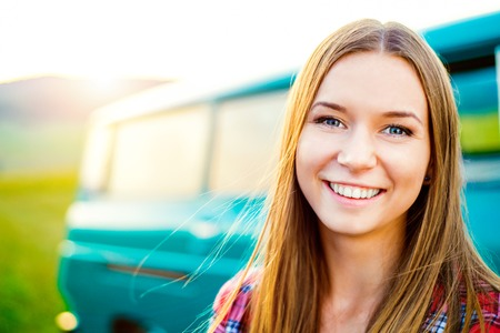 campervan: Teenage girl with long hair smiling against green campervan outside in sunny nature Stock Photo
