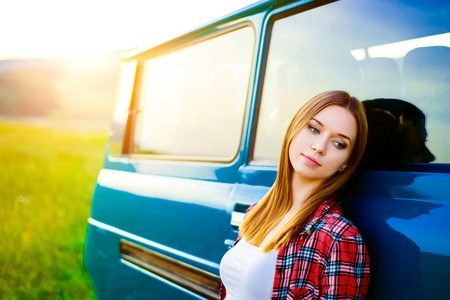 leaning against: Teenage girl with long hair smiling leaning against green campervan outside in sunny nature