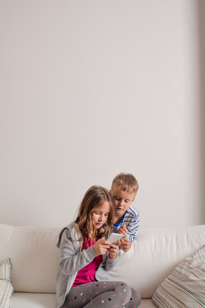 kids room: Little girl and boy sitting on sofa with a smart phone at home. Happy children playing indoors, copy space Stock Photo
