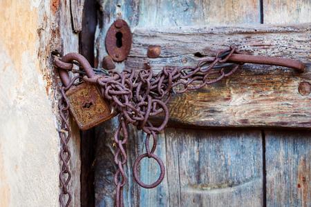 puertas antiguas: cerradura de puerta de la vendimia y de la cadena oxidada en una antigua puerta de madera marrón