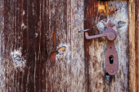 Rusty vintage door handle on an old brown wooden door Stock Photo