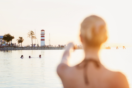 woman pointing: Young girl in a bikini near the shoreline, lighthouse in the background, sunny summer