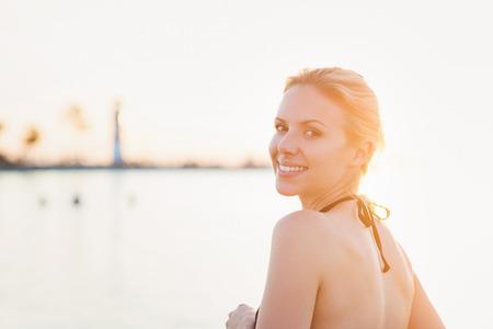 Jong meisje in een bikini poseren in de buurt van de kust, vuurtoren op de achtergrond, zonnige zomer Stockfoto