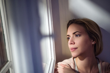 Beautiful blond woman sitting on window sill at night, looking out of window