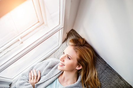 sill: Beautiful blond woman lying on window sill smiling, looking out of window