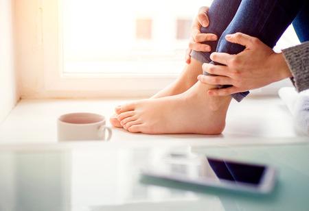 jolie pieds: Pieds de femme méconnaissable assis sur rebord de la fenêtre avec un téléphone intelligent et tasse de café Banque d'images