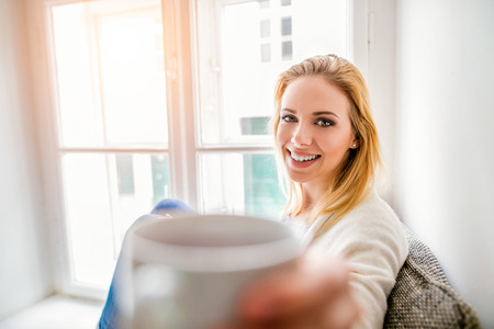 window sill: Beautiful blond woman sitting on window sill holding a cup of coffee