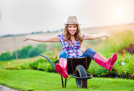 Beautiful woman in rubber boots and hat sitting in wheelbarrow in sunny green garden Banque d'images