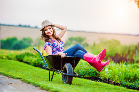 rubber boots: Beautiful woman in rubber boots and hat sitting in wheelbarrow in sunny green garden Stock Photo
