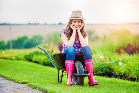 rubber plant: Beautiful woman in rubber boots and hat sitting in wheelbarrow in sunny green garden Stock Photo
