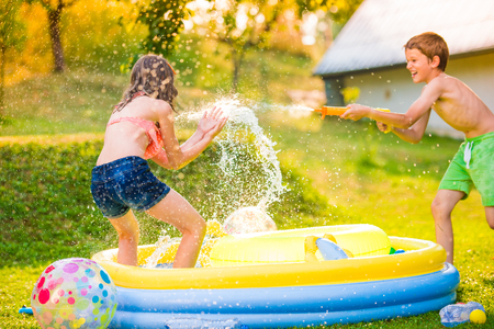 mujer ba�andose: Boy splashing girl with water gun in garden swimming pool, sunny summer day, back yard