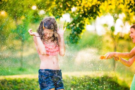 water garden: Boy splashing girl with water gun, fun in garden, sunny summer day, back yard