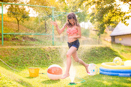 Girl running above a sprinkler, sunny summer back yard, garden swimming pool