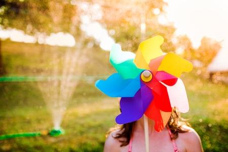 water garden: Beautiful girl in swimsuit hiding behind colorful pinwheel, sunny summer garden Stock Photo
