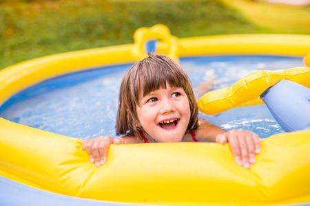 personas banandose: Ni�a linda que se divierte en piscina amarilla jard�n. Soleado d�a de verano en el patio trasero