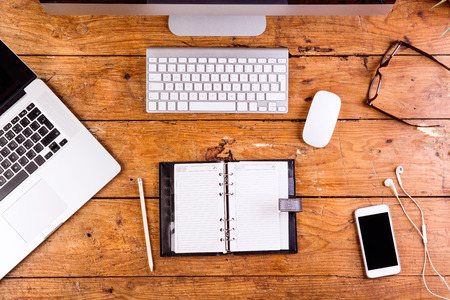 personal organizer: Desk with gadgets and office supplies. Computer keyboard, notebook, personal organizer, smart phone and stationery around the workplace. Flat lay.