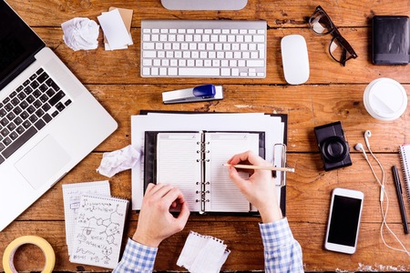 person writing: Business person at office desk writing and working. Smart phone, camera, notepad and eyeglasses and various office supplies around the workplace. Flat lay.