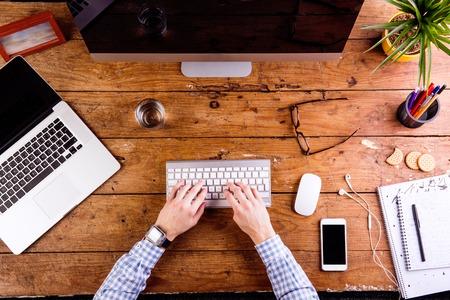 비즈니스 사람, 사무실 책상에 컴퓨터 키보드에 쓰기. 테이블에 손을 스마트 폰에 스마트 시계. 물, 메모장 및 안경 및 직장 주위에 다양한 사무 용품의