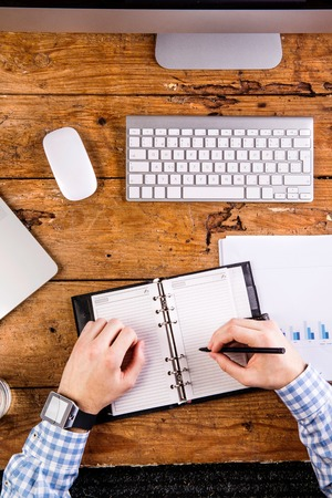 person writing: Business person at the office desk writing into personal organizer, wearing smart watch on hand. Flat lay.