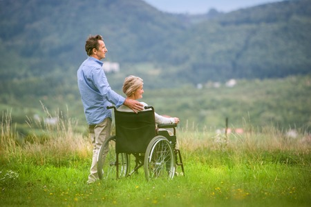 rear view: Senior man with woman sitting in wheelchair oustide in green autumn nature, rear view Stock Photo