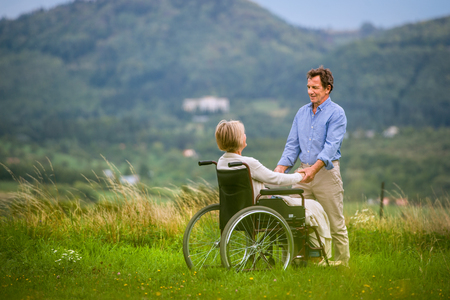 couple nature: Senior man with woman sitting in wheelchair, holding hands, oustide in green autumn nature, rear view