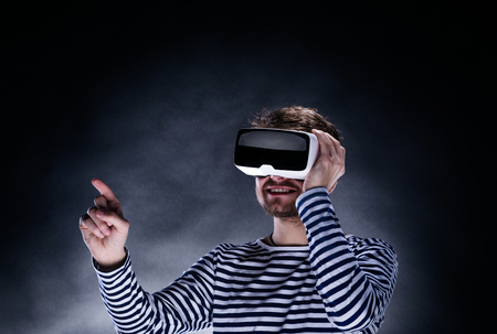 Hipster man in striped black and white sweatshirt wearing virtual reality goggles. Studio shot on black background 免版税图像