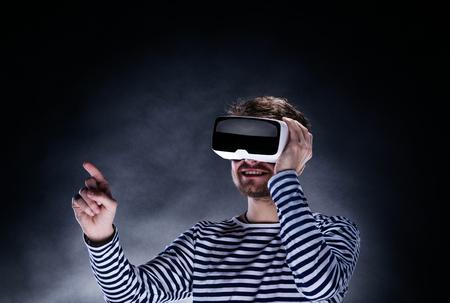homem moderno na camisola preta e branca listrada usando óculos de realidade virtual. O estúdio disparou no fundo preto